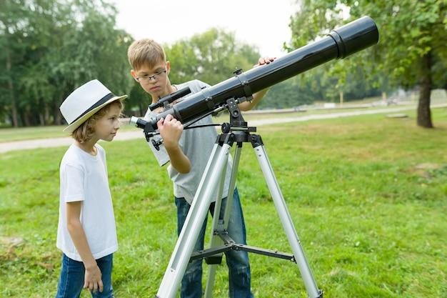 Kinderjugendliche im park, der durch ein teleskop schaut