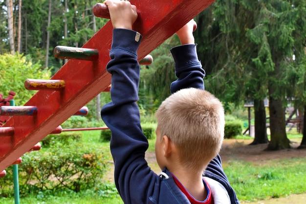 Kinderjunge auf horizontaler leiste auf dem spielplatz.