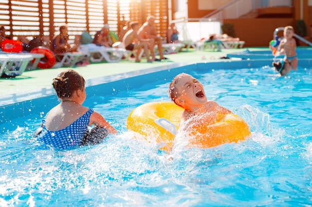 Kinderjunge, der außenpool des resorts spielt. in einem aufblasbaren gelben kreis mit einem ball. kinder tummeln sich mit wasserspielzeug. plantschen herum. hitze auskühlen lassen.