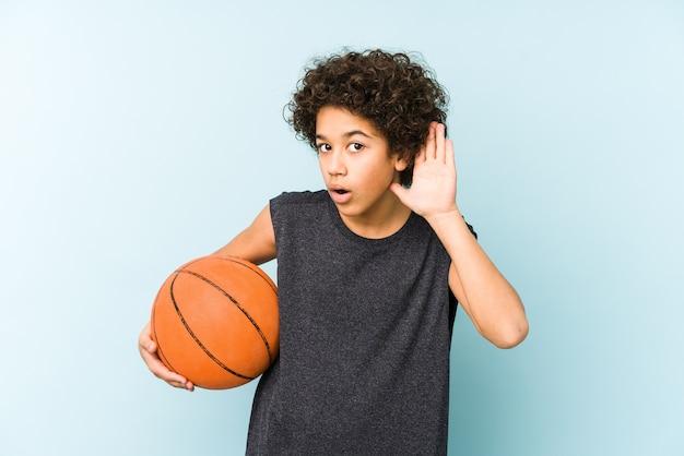 Kinderjunge, der basketball spielt, isoliert auf blauer wand, die versucht, einen klatsch zu hören.