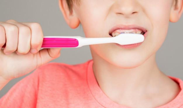 Kinderjunge, der die zähne putzt. junge zahnbürste weiße zahnpasta. gesundheitsversorgung, zahnhygiene. frohes kind zeigt zahnbürsten. zähneputzen des kleinen jungen. zahnhygiene. glückliches kleines kind, das sich die zähne putzt.