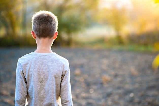 Kinderjunge, der draußen am sonnigen sommertag steht und warmes wetter draußen genießt. ruhe- und wellnesskonzept.