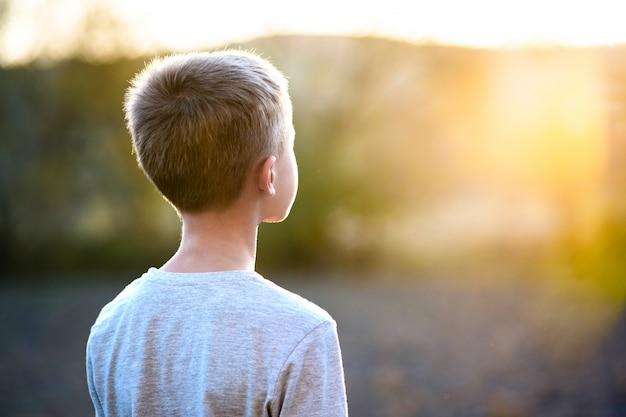 Kinderjunge, der draußen am sonnigen sommertag steht und warmes wetter draußen genießt