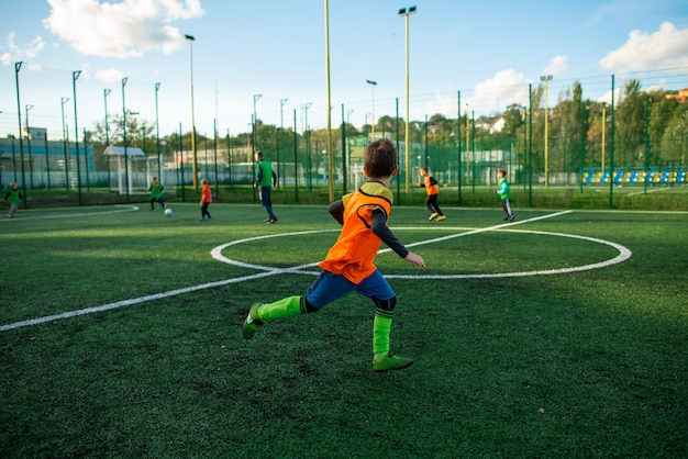 Kinderjunge, der fußball auf feld spielt. schulfußballstadion, grüner grashintergrund.