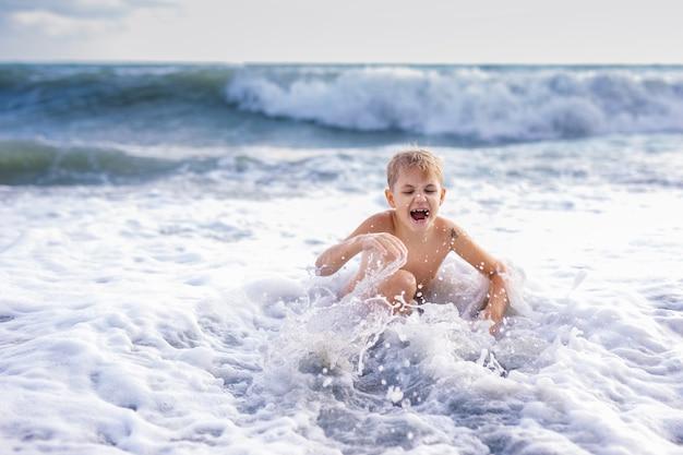 Kinderjunge, der in den wellen auf dem strand im sommersonnenuntergang spielt