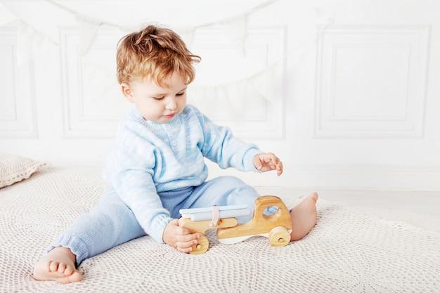 Kinderjunge, der in seinem raum mit einem hölzernen spielzeugauto spielt.