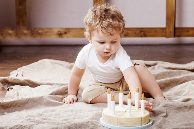 Kinderjunge, der in seinem raum mit einem hölzernen spielzeugkuchen spielt