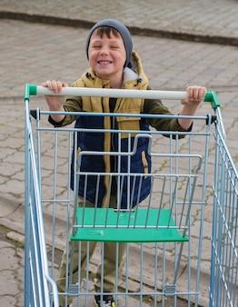 Kinderjunge, der leeren einkaufswagen am parkplatz schiebt