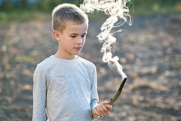 Kinderjunge, der mit dem rauchenden hölzernen stock draußen spielt.