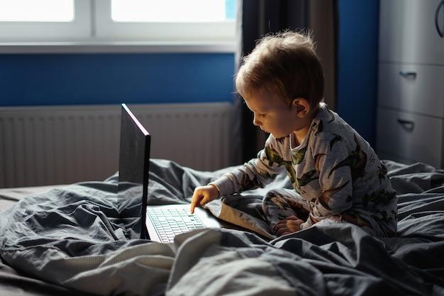 Kinderjunge, der mit laptop spielt, während er auf dem bett liegt. das kind spricht über einen videoanruf junge, der einen film im laptop sieht