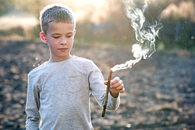 Kinderjunge, der mit rauchendem holzstab draußen spielt.