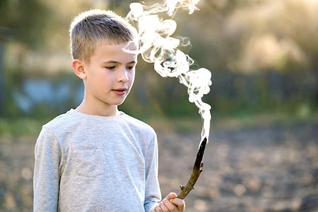 Kinderjunge, der mit rauchendem holzstab draußen spielt