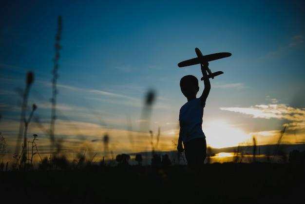 Kinderjunge, der mit spielzeugflugzeug während der sonnenuntergangszeit spielt