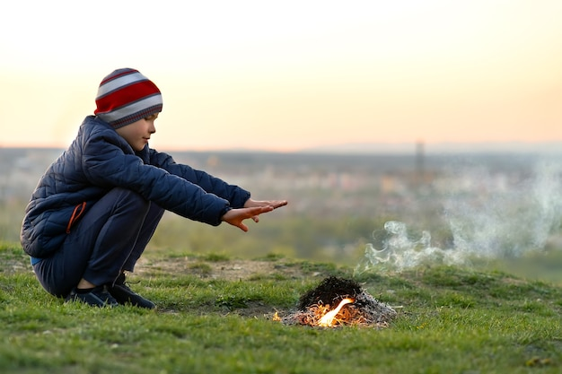 Kinderjunge, der nahe lagerfeuer draußen im kalten wetter wärmt.
