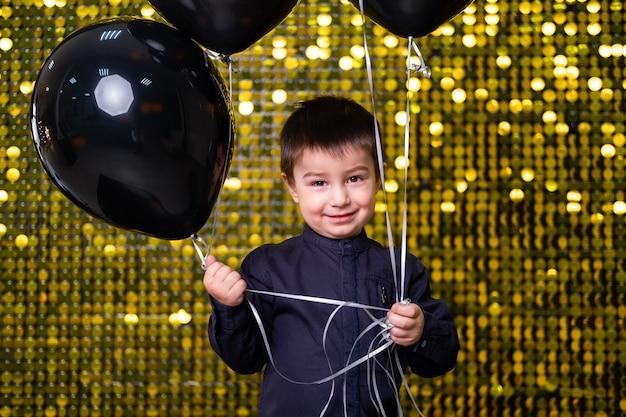 Kinderjunge, der schwarze ballons auf dem hintergrund mit goldglänzenden pailletten, pailletten hält.