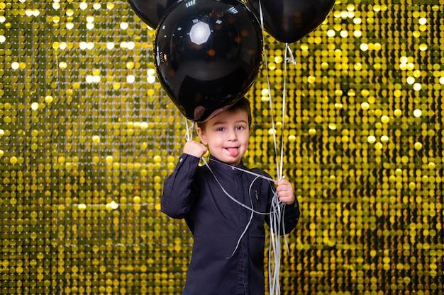 Kinderjunge, der schwarze luftballons auf dem hintergrund mit goldglänzenden pailletten-pailletten hält