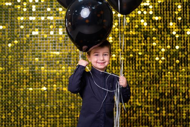 Kinderjunge, der schwarze luftballons auf dem hintergrund mit goldglänzenden pailletten-paillettes hält