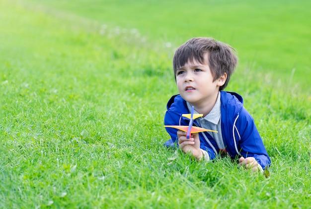 Kinderjunge, der sich auf grünem gras hinlegt und oben mit neugierigem gesicht schaut