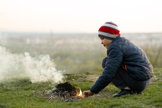 Kinderjunge, der sich bei kaltem wetter im freien in der nähe von lagerfeuer erwärmt.