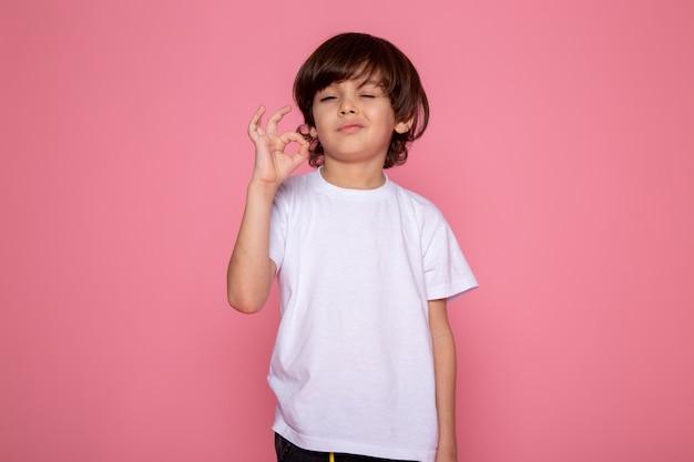 Kinderjunge, der zeichen entzückend niedlich auf rosa wand zeigt