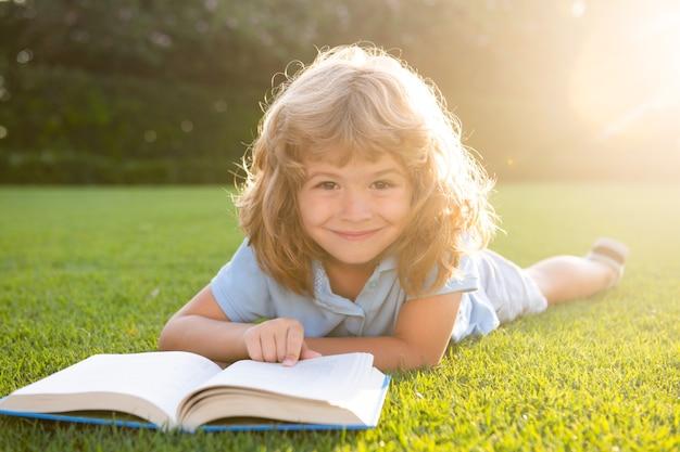 Kinderjunge liest interessenbuch im garten sommerspaß süßer junge liegt auf dem gras und liest ein kind...