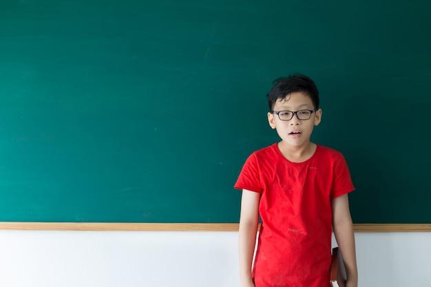 Kinderjunge machen nerdgesicht und stagingg auf tafel im klassenzimmer in der schule