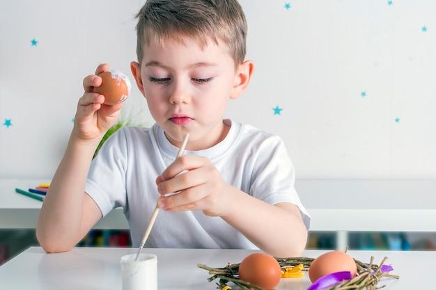 Kinderjunge malt eier mit weißer farbe. diyy-konzept.