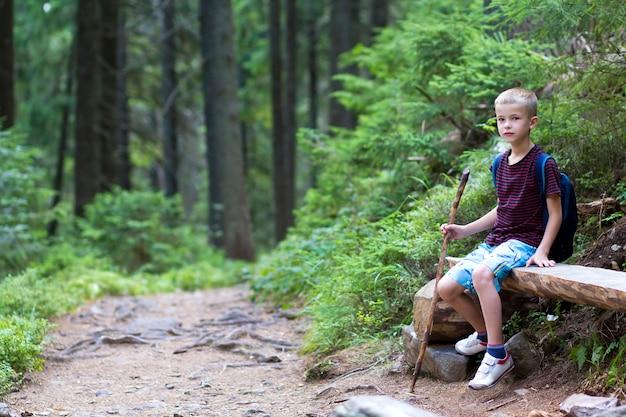 Kinderjunge mit dem stock und rucksack, die allein auf baumstamm sitzen