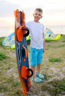 Kinderjunge mit einem brett für das schwimmen oder surfen, die auf dem meer lächeln