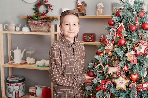 Kinderjunge mit geschenkbox und weihnachtsbaum.