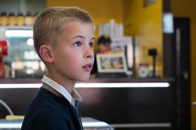 Kinderjunge sitzt im fast-food-restaurant hinter leerem tisch und wartet auf essen.
