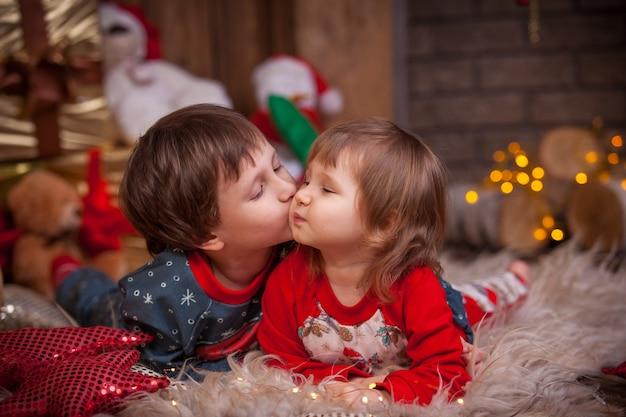 Kinderjunge und -mädchen, die auf dem boden nahe dem weihnachtsbaum mit geschenken für den feiertag liegen. süßer kuss auf die wange. kinder im pyjama