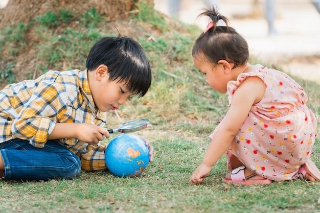 Kinderjunge und -mädchen, die globus für das lernen der weltkarte betrachten