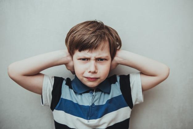 Kinderjunge vor grauem hintergrund, der ohren mit den händen bedeckt. konzept der häuslichen gewalt und des missbrauchs in der familie