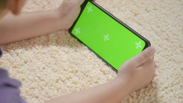 Kinderjunge vorschule mit gadget, das videospiele auf handy spielt
