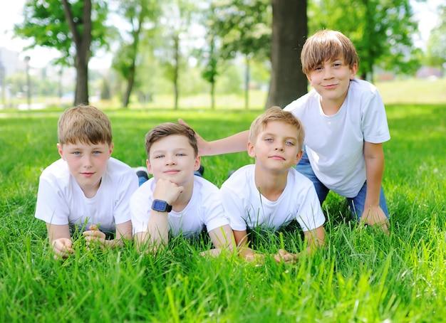 Kinderjungen haben spaß und spielen auf dem gras und dem park. freundschaft, camping, urlaub