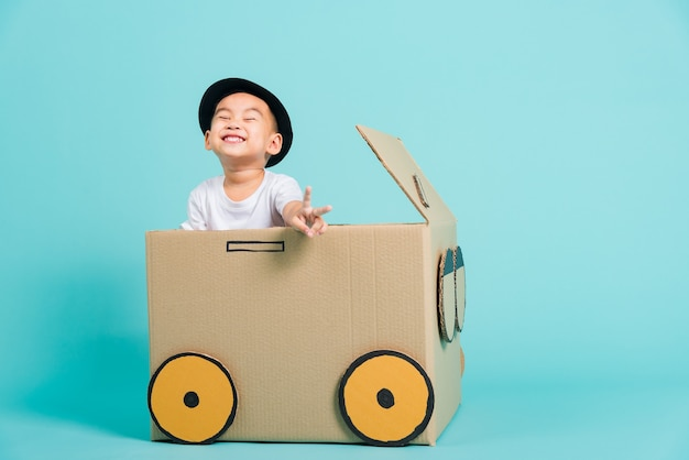 Kinderjungen lächeln im fahrenden spielauto kreativ durch eine pappkartonphantasie