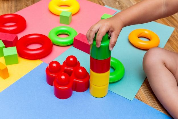 Kinderkind, das bunte bildungsspielzeuge auf dem hellen hintergrund spielt. kindheit kinder kinder babys konzept.