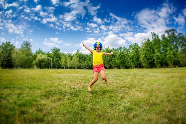 Kinderkindermädchen mit lustigem glücklichem offenem armausdruck und girlanden der blauen perücke des parteiclowns springt in den park