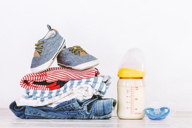 Kinderkleidung und -flasche mit milch auf holztisch