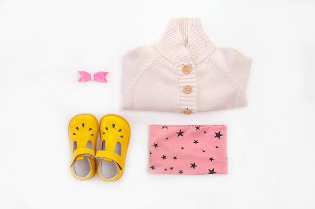Kinderkleidung und schuhe sind auf einer weißen hintergrundoberansicht ausgelegt. platz für den text.