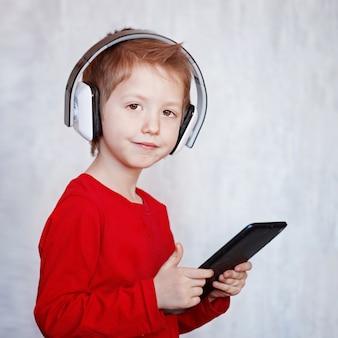 Kinderkleiner junge, der musik hört oder film mit kopfhörern aufpasst und die digitale tablette, spielend verwendet.