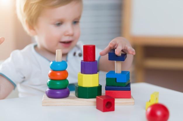 Kinderkleiner junge, der zu hause hölzerne spielzeugpyramide oder -kindergarten spielt