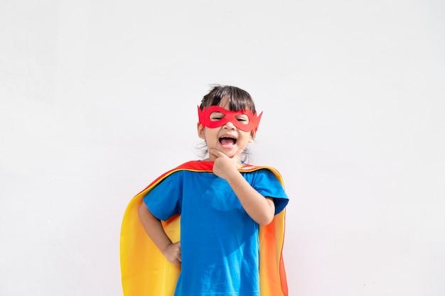 Kinderkonzept, lächelndes mädchen, das superheld auf weißem hintergrund spielt