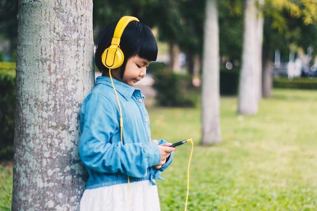 Kinderkonzept und -technologie - lächelndes mädchen mit kopfhörern hörend musik