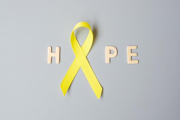 Kinderkrebs, sarkom, knochen, blase und suizidprävention awareness-monat, goldgelbes band zur unterstützung von menschen, die leben und krank sind. kindergesundheits- und weltkrebstagkonzept
