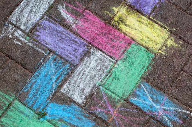 Kinderkreidebild auf dem bürgersteig. mehrfarbige kreidezeichnung der kinder auf dem asphalt. hintergrund, draufsicht von oben.