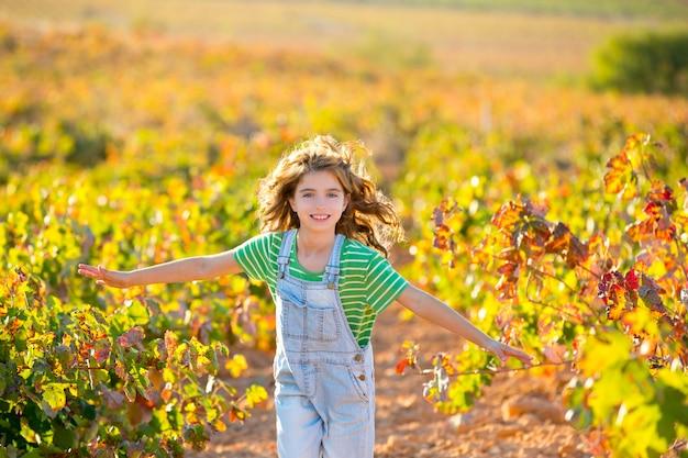 Kinderlandwirtmädchen, das im herbst im weinbergfeld läuft