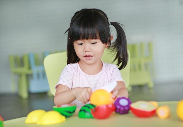 Kindermädchen am tisch spielt künstliche frucht im kinderraum.