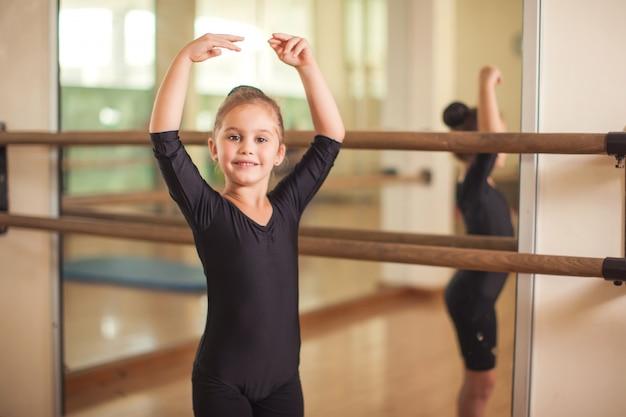 Kindermädchen an der gymnastikklasse, die übungen macht. kinder- und sportkonzept